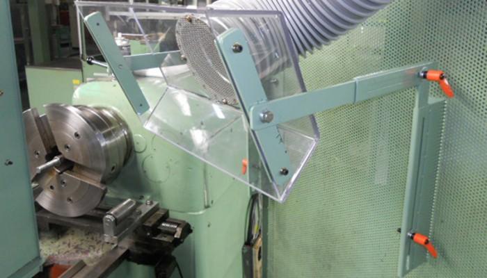 フード製作取付旋盤機より発生する加工時の油煙を吸い込むための透明塩ビ製フード。位置を調整できるように設置しました。