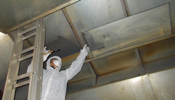 換気フードの表面に付着した汚れの清掃作業。
